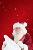 Santa claus writing on scroll — Stockfoto