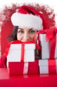 Composite image of festive brunette holding stack of gifts  — Stock Photo