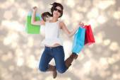 Composite image of happy brunette jumping with shopping bags — Foto de Stock