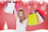Blonde woman raising shopping bags — Stock Photo