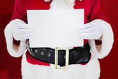 Composite image of mid section of santa claus holding page — Stock Photo
