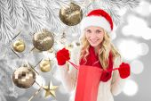 Happy festive blonde with shopping bag — Stock fotografie