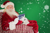 Santa using tablet on the armchair — Stock Photo