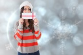Composite image of festive brunette holding a gift  — Stock Photo