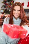 Festive redhead with gift on the couch — Stock fotografie