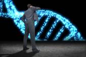 Businessman against blue glittering dna helix — Stock fotografie