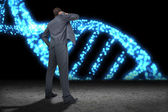 Businessman against blue glittering dna helix — Stock Photo