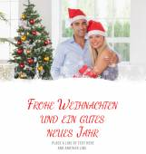 Composite image of happy couple at christmas — Stock Photo