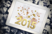 Golden 2015 against tablet pc — Stockfoto