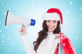 Brunette holding gift bags and megaphone — Stock Photo