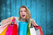 Composite image of overwhelmed young woman with shopping bags — ストック写真