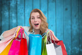 Composite image of overwhelmed young woman with shopping bags — Stock Photo