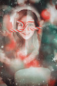 Happy little girl in santa hat holding candy — Foto de Stock