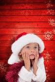 Composite image of cute little girl wearing santa hat and tinsel — Stockfoto