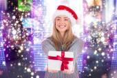 Festive blonde holding christmas gift — Stock Photo