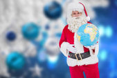Happy santa claus holding a globe — Foto Stock