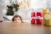 Festive little boy looking at gifts — Stock Photo