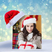 Festive brunette showing gift at christmas — Stock Photo