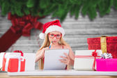 Composite image of festive blonde writing her christmas list — Stock fotografie