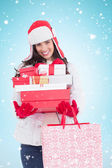 Brunette in winter clothes holding many gifts — ストック写真