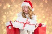 Composite image of woman in santa hat offering a gift — Stock Photo