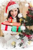 Festive brunette holding pile of gifts — Fotografia Stock