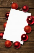 Composite image of red christmas baubles surrounding white page — Foto de Stock