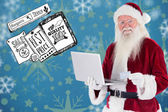 Santa pays with credit card on a laptop — Stock Photo