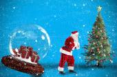 Composite image of santa pulling snow globe of presents — Stock Photo