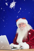 Santa surfs on internet — Stock Photo