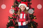 Festive little girl holding gifts — Stock Photo