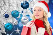 Happy festive blonde with shopping bag — Stok fotoğraf