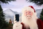 Santa Claus shows smartphone — Stock Photo