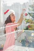 Brunette decorating christmas tree — Stock Photo