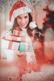 Festive brunette holding pile of gifts — 图库照片