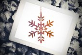 Hanging snowflake against tablet — Stock Photo