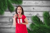 Composite image of excited brunette opening a christmas gift — Stock Photo
