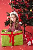 Festive girl sitting in large gift — Stock Photo
