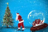 Composite image of santa pulling snow globe of presents — Zdjęcie stockowe
