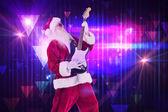 Santa playing electric guitar — Stock Photo
