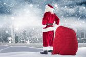 Santa standing on snowy ledge — Stock Photo