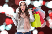 Composite image of excited brunette with shopping bags — Stock Photo