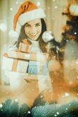 Festive brunette holding pile of gifts — Stock Photo