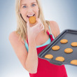Happy blonde eating hot cookies — Stock Photo #62481321