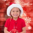 Composite image of cute little girl wearing santa hat holding ba — Stock Photo #62482337