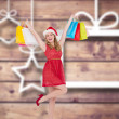 Pretty woman in santa hat holding up shopping — Stock Photo #62484073