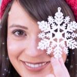 Festive brunette holding snowflake decoration — Stock Photo #62486219