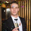 Handsome man holding flute of champagne — Stock Photo #62487551