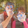 Couple blowing noses into tissues — Stock Photo #62488501