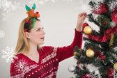Woman hanging christmas decorations on tree — Stock Photo